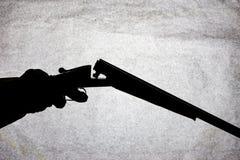 Double-barrell fusil de chasse lisse classique sur la main de l'homme d'isolement sur le fond en pierre clair photos stock