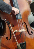 Double bass being plucked. Detailof double bass being plucked by the hand of an elderly player, with bow in a pouch Royalty Free Stock Images