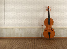 Double-bass in a empty retro room. Double-bass  leaning against a brick wall in an empty room Royalty Free Stock Image