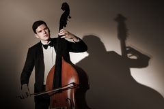 Double bass player playing contrabass. Classical musician studio portrait Royalty Free Stock Image