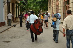 Double Bass Player walking through old Havanna. Double Bass Player, musician, walking with the timbalero, through the old Havanna, Cuba Royalty Free Stock Images
