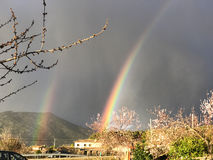 Double beautiful rainbow on countryside on blooming at springtim Royalty Free Stock Photography