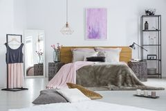 Double bed with fur duvet. Decorative cushions lying in front of a double bed with fur duvet and metal nightstands in bright female room Stock Photos