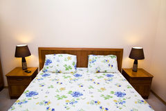 Double bed in hotel room. Double bed with bedside tables in a hotel room Stock Photography