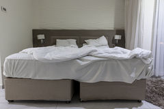 Double bed in a hotel room with messed bed Royalty Free Stock Photography