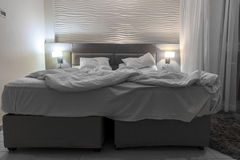 Double bed hotel room with messed bed night light Stock Photo