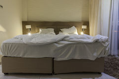 Double bed hotel room with messed bed reading light Royalty Free Stock Photography