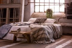 Bed with pillows and blanket, wooden stool and plant in a wabi sabi bedroom royalty free stock photos