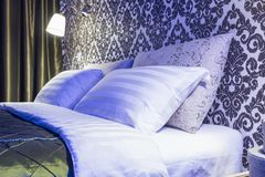 Double bed with pillows in interior of the modern bedroom in loft flat in bright color style of expensive apartments in neon light stock photography
