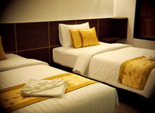Double bed room with gold brown yellow colour pillows. Close up photo of hotel double bed room with gold brown yellow colour pillows in white painted wall Stock Images