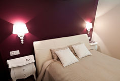Purple bedroom. Double bed and wall lamps of a purple color theme bedroom Stock Image