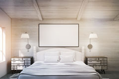 Double bed in a wooden room with poster, toned Royalty Free Stock Photo