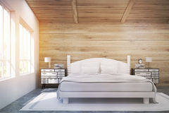 Double bed in a wooden room, toned Royalty Free Stock Image