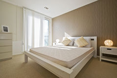 Double bedroom in white. Modern designer bedroom in white with brown wave pattern wallpaper royalty free stock photo