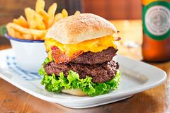 Double beef burger with lettuce, bacon, cheese. Fries and beer in restaurant. Stock Image