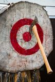 Axe in red and white target. Double bitted axe with wooden handle stuck in a log end painted as a red and white target stock images