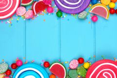 Double border of colorful assorted candies against blue wood Royalty Free Stock Photography