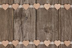 Double border of wooden hearts and ribbon lace over wood Royalty Free Stock Photo