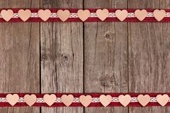 Double border of wooden hearts and ribbon over rustic wood Stock Images