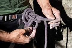 Double bowline knot. Mountain climber tying rope in double bowline knot royalty free stock photo