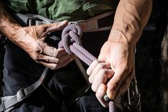 Double bowline knot. Mountain climber tying rope in double bowline knot stock image