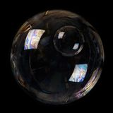 Double bubble. Double poured soap bubble on a black background Royalty Free Stock Images