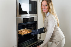 Double burden: business woman baking cookies in the kitchen Stock Photo