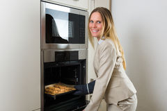 Double burden: business woman baking cookies in the kitchen Royalty Free Stock Image