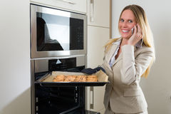Double burden: business woman baking cookies in the kitchen Royalty Free Stock Photos