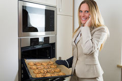 Double burden: business woman baking cookies in the kitchen Stock Photography