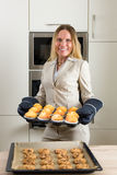 Double burden: business woman baking cupcakes in the kitchen Royalty Free Stock Photo