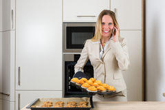 Double burden: business woman baking cupcakes in the kitchen Stock Photos