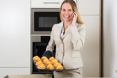 Double burden: business woman baking cupcakes in the kitchen. Double burden: attractive business woman baking cupcakes in a modern kitchen and having Stock Photography
