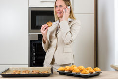 Double burden: business woman baking cupcakes in the kitchen Royalty Free Stock Photography