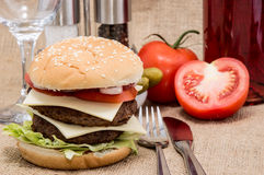 Double Burger with ingredients and cutlery Royalty Free Stock Photo
