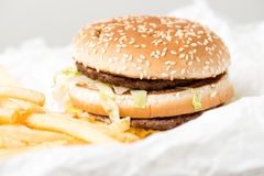Double burger from McDonalds. Double burger with french fries on white paper Stock Photography