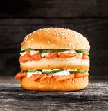 Double burger with salmon. Cucumber and sauce on a rustic background stock image