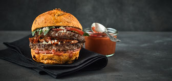Double burger served with dip of sauce Stock Images