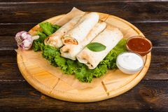 Double burrito with chicken in Caesar sauce on a dark wooden background royalty free stock photography