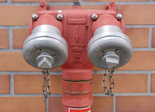 Double capped red fire hydrant. In front of a brick wall on a building with closed valves ready for an emergency Royalty Free Stock Photos