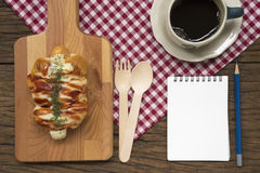 Double Cheese Sausage Bun. And black coffee on wooden table. Top view with opened notepad Stock Photography