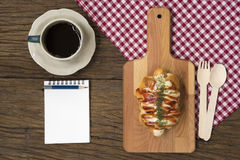 Double Cheese Sausage Bun. And black coffee on wooden table. Top view with opened notepad Stock Photos