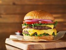 Double cheeseburger avec de la laitue, la tomate, l'oignon, et le fromage américain fondu image stock