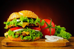 Double cheeseburger and fresh vegetables Royalty Free Stock Image