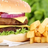 Double cheeseburger hamburger with fries closeup close up. Beef tomatoes cheese unhealthy Royalty Free Stock Photos