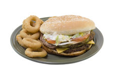 Double cheeseburger onion rings. Double stack cheeseburger with tomato, lettuce, onions, mayo, pickles and onion rings on a green plate isolated on white Stock Images