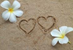 Double coeur dessiné sur le sable Image stock