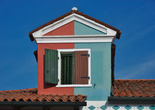 Double-colored mansard roof dormer in Burano, Italy. Two-colored tiled mansard roof gable dormer window with blinds in Burano island, Italy stock images