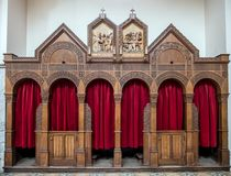 Double confessional. Ornamental double wooden confessional with red drapes in catholic church Royalty Free Stock Images