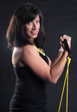 Double Curl. Woman wearing a black tank top working out with yellow fitness bands Stock Photography